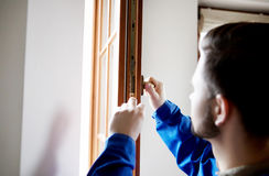 Young handyman repair window with screwdriver Stock Photo