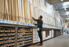 Young handyman selecting a length of cut timber Royalty Free Stock Image