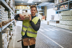 Young handyman selecting supplies in a warehouse Stock Images