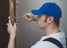 Young handyman. Young handyman in uniform changing door lock royalty free stock image