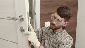 Young handyman in uniform fixing door lock.