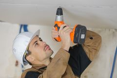 Young handyman using cordless drill to pierce ceiling Royalty Free Stock Photography