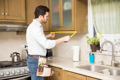 Handyman measuring a kitchen cabinet Royalty Free Stock Photos