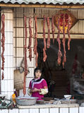 Young Hani Girl selling Sausage Stock Photography
