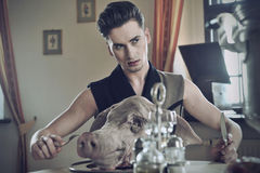 Young hansome fashioned men eat pig Stock Photography