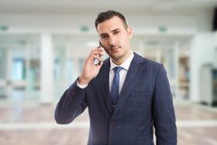 Young hansome realtor using smartphone stock photography