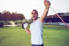 Happiness winner man golfer putting a golf ball in to hole royalty free stock image