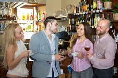 Young happy adults at bar. Casual acquaintance of happy young adults at bar. Selective focus Stock Image