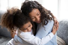 Happy African American mom and daughter hug making peace stock photos
