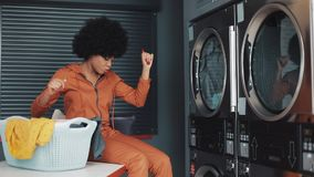 Young happy African American woman with curly hair funny dancing in the self-service public laundry. stock video