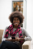 Black woman sitting on sofa and using mobile phone. Young happy african american woman sitting on sofa and using mobile phone at luxury home Stock Image