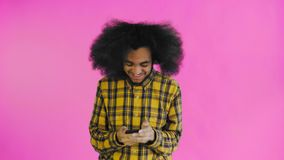 Young happy African businessman using phone and getting good news on purple background. Concept of emotions. 4K stock footage