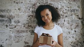 Portrait of Young happy african girl holding gift box and smiling into camera. Young happy african girl holding gift box and smiling into camera Royalty Free Stock Photos