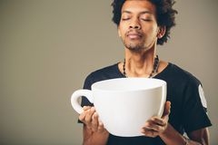 Man holding funny huge and oversized cup of black coffee Stock Photos