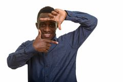 Young happy African man smiling and focusing with fingers. Isolated against white background stock photography