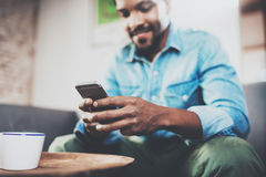 Young happy African man using smartphone while sitting on sofa at home.Concept people working with mobile gadget Stock Photography