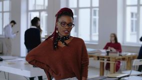 Young happy African sales professional business woman in eyeglasses smiling, becoming serious posing at trendy office. Positive focused black female start-up stock video footage