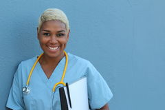 Young happy afro american nurse standing at hospital ward with clipboard and pen in hand. Smiling, looking at camera Royalty Free Stock Images