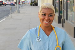 Young happy afro american nurse standing outside of the hospital in the city streets. Smiling, looking at camera Stock Photo