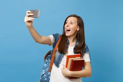 Young happy amazed woman student with opened mouth with backpack holding school books doing taking selfie shot on mobile royalty free stock photography
