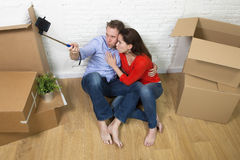 Young happy American couple sitting on floor celebrating moving in new house apartment or flat Royalty Free Stock Photos