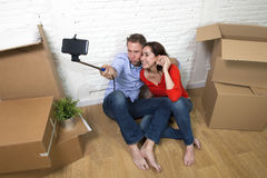 Young happy American couple sitting on floor taking selfie photo celebrating moving in new house or apartment Royalty Free Stock Photo