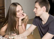 Young happy amorous couple celebrating with white wine at restaurant Royalty Free Stock Images