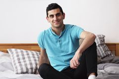 Happy arabic man smiling, sitting on bed at home stock photos