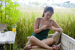 Happy Asian Chinese woman on her 20s or 30s smiling having fun using internet on mobile phone drinking orange juice sitting outdoo Stock Photography