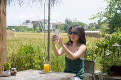 Asian Chinese woman on her 20s or 30s smiling having fun using internet on mobile phone shooting selfie or chatting drinking orang Stock Image