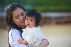 Young happy Asian Chinese woman mother of adorable baby girl holding her sweet little daughter in her arms taking a walk at royalty free stock photo