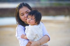 Young happy Asian Chinese woman mother of adorable baby girl holding her sweet little daughter in her arms taking a walk at stock photos