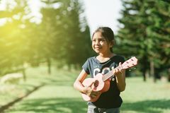 Young and happy asian girl playing ukelele guitar in the park at sunny morning while looking to copy space. Hobbies and tranquility concept Royalty Free Stock Photography