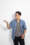 Young happy asian man smile to the camera, prensenting hand gest Stock Photo
