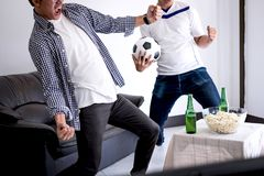 Young Happy Asian Men family or football fans watching soccer ma. Tch on tv and cheering football team, celebrating with drink beer and eat popcorn at home Stock Images