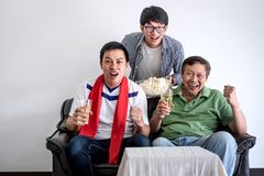Young Happy Asian Men family or football fans watching soccer ma. Tch on tv and cheering football team, celebrating with drink beer and eat popcorn at home Stock Photo
