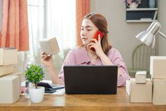 Young happy asian online business woman in her home talking on h. Er phone with her customer while looking at box of product, good for home business or online Stock Image