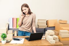 Young happy asian online business woman in her home talking to h. Er customer on her phone while looking at boxes of product, good for home business, online Royalty Free Stock Images