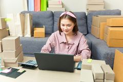 Young happy asian online business woman working on her computer. At home in her living room surrounded by boxes of her products, good for home business or Stock Photography