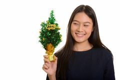 Young happy Asian teenage girl smiling and holding Happy New Yea