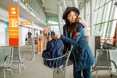 Young asian traveller in warm clothes stands with bags looking at the smartphone at the hall of airport. stock images