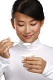 Young happy asian woman eating fresh yogurt. On white Stock Photos
