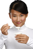 Young happy asian woman eating fresh yogurt. On white Royalty Free Stock Photos