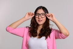 Young happy Asian woman with hands on eyeglasses. Portrait of young happy Asian woman with hands on eyeglasses royalty free stock image