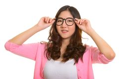 Young happy Asian woman with hands on eyeglasses. Isolated against white background stock photo