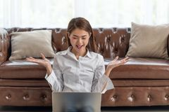 Young happy Asian woman with laptop celebrating with hands raised up royalty free stock photography