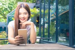 young happy asian woman looking smiling at camera, wearing earphone and holding her phone royalty free stock image