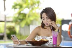 Young happy Asian woman in sexy dress outdoors having brunch or. Young beautiful and happy Asian woman in sexy dress sitting at pool holiday resort having brunch Royalty Free Stock Photo