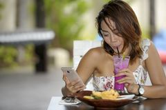 Young happy Asian woman in sexy dress outdoors having brunch or. Young beautiful and happy Asian woman in sexy dress sitting at pool holiday resort having brunch Stock Images
