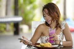 Young happy Asian woman in sexy dress outdoors having brunch or. Young beautiful and happy Asian woman in sexy dress sitting at pool holiday resort having brunch Stock Photos